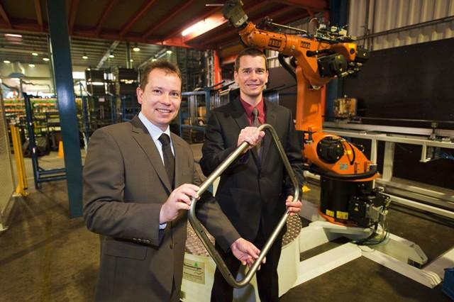 Hinrich und Jochen Fechtel halten eine Stahlstange und stehen vor einer Maschine