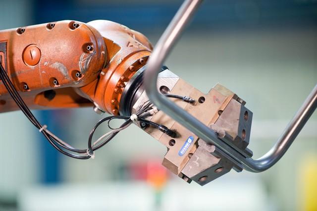 Roboter mit Stahlrohr in der Klemme