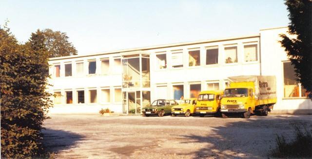 Vor dem Gebäude stehen ein paar Autos und Transporter